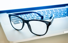 Computer goggles on a laptop, close-up view. Blue light blockers resting on computer keyboard, eye fatique problem concept