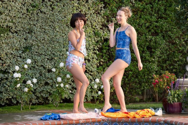 """PEN15 -- """"Pool"""" - Episode 201 -- Two days after the dance, Maya and Anna reluctantly go to a lame pool party. A crush unexpectedly shows up, causing them to question their sanity and reputations. Maya Ishii-Peters (Maya Erskine) and Anna Kone (Anna Konkle), shown. (Photo by: Erica Parise/Hulu)"""