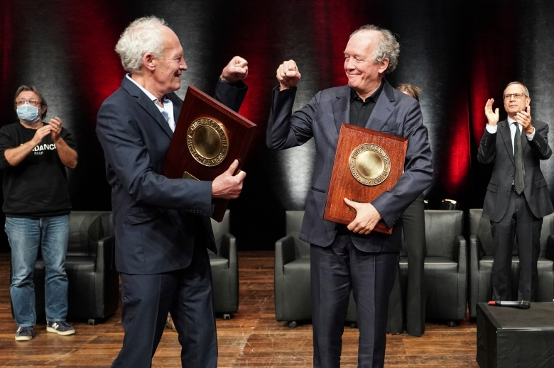 Belgian directors Luc and Jean-Pierre Dardenne celebrate after receiving their Awards during the Lumiere Award ceremony of the 12th Lumiere Festival, in Lyon, central France, Friday, Oct. 16, 2020. (AP Photo/Laurent Cipriani)