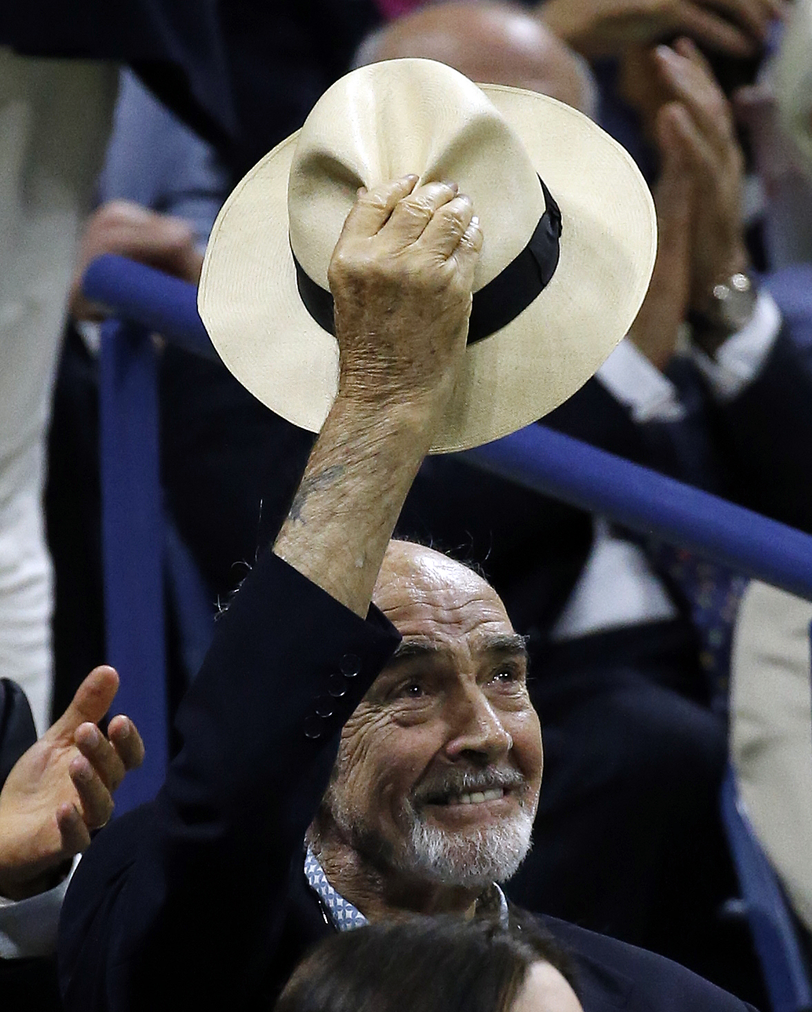 Sean Connery acknowledges the crowd during the men's championship match between Roger Federer and Novak Djokovic at the U.S. Open tennis tournament, Sunday, Sept. 13, 2015, in New York. (AP Photo/Julio Cortez)