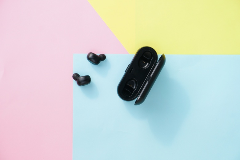 Black true wireless earbuds headphones with power bank case over colorful pastel color.