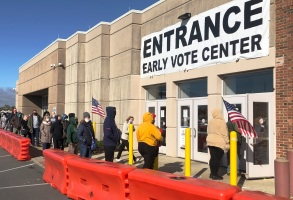 FILE - In this Friday, Oct. 30, 2020 file photo, people bundled against the cold stand in a slowly moving line to cast early votes at the Franklin County Board of Elections in Columbus, Ohio. Early voting ends in Ohio on Monday, Nov. 2. A surge in coronavirus cases across the country, including in key presidential battleground states, is creating mounting health and logistical concerns for voters, poll workers and political parties ahead of Election Day. (AP Photo/Andrew Welsh-Huggins)
