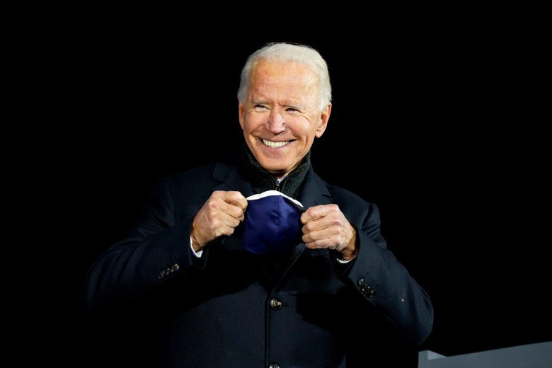 Democratic presidential candidate former Vice President Joe Biden smiles as he puts on a face mask during a drive-in rally at Lexington Technology Park, Monday, Nov. 2, 2020, in Pittsburgh. (AP Photo/Andrew Harnik)