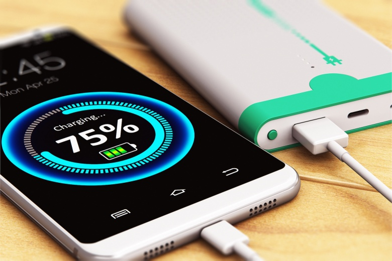 3D render illustration of the macro view of smartphone or mobile phone charging by a portable power bank rechargeable battery pack on the wooden table with selective focus effect