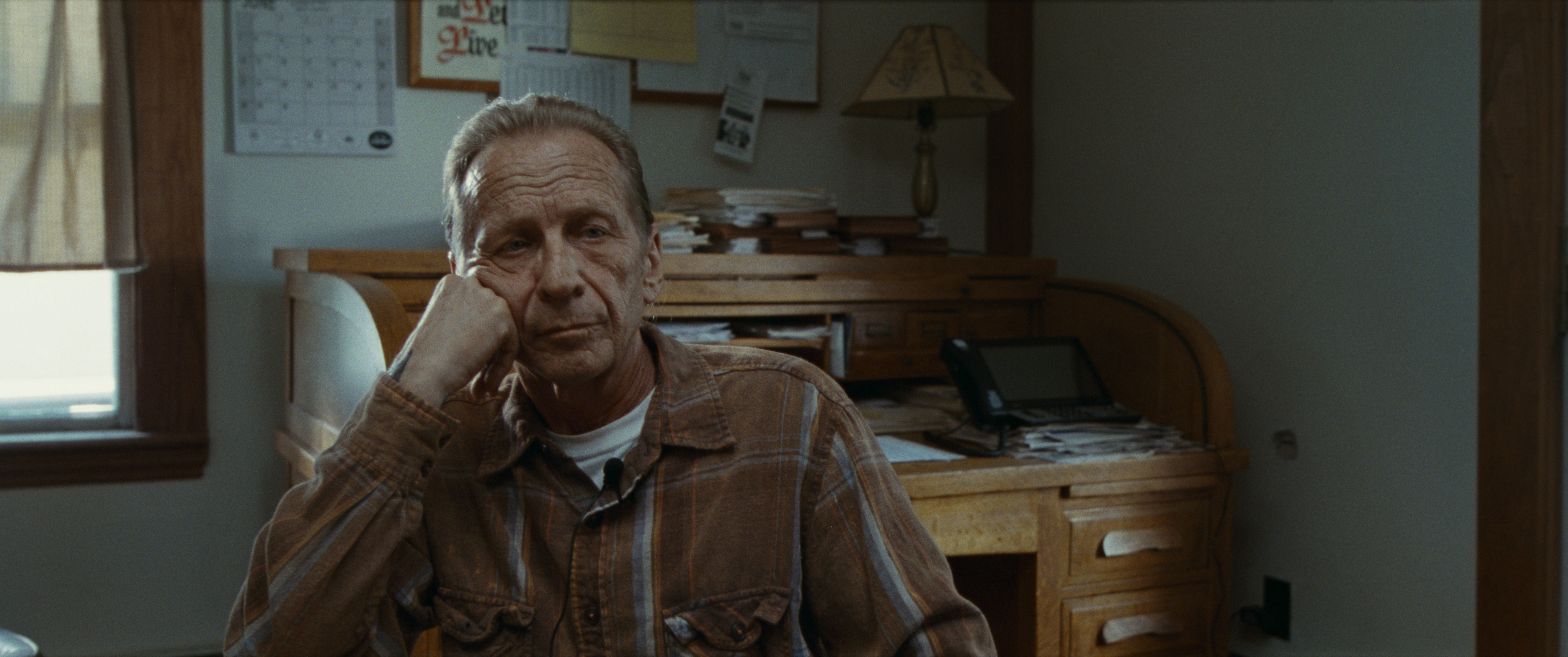 Image is from the film 'Sound of Metal (2019). A man in his fifties sits in a office with his head resting against his fist. He is wearing a brown plaid shirt.