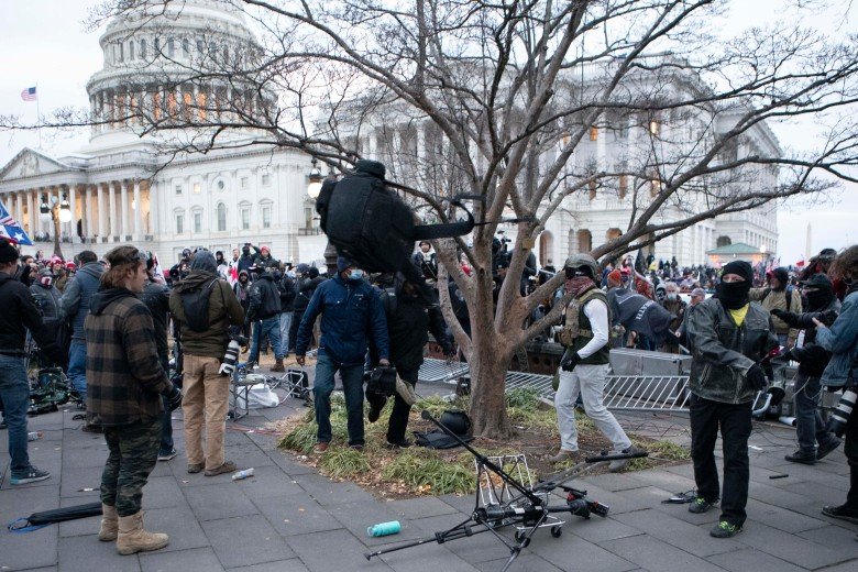 Protesters break television equipment outside the the U.S. Capitol on Wednesday, Jan. 6, 2021, in Washington. (AP Photo/Jose Luis Magana)