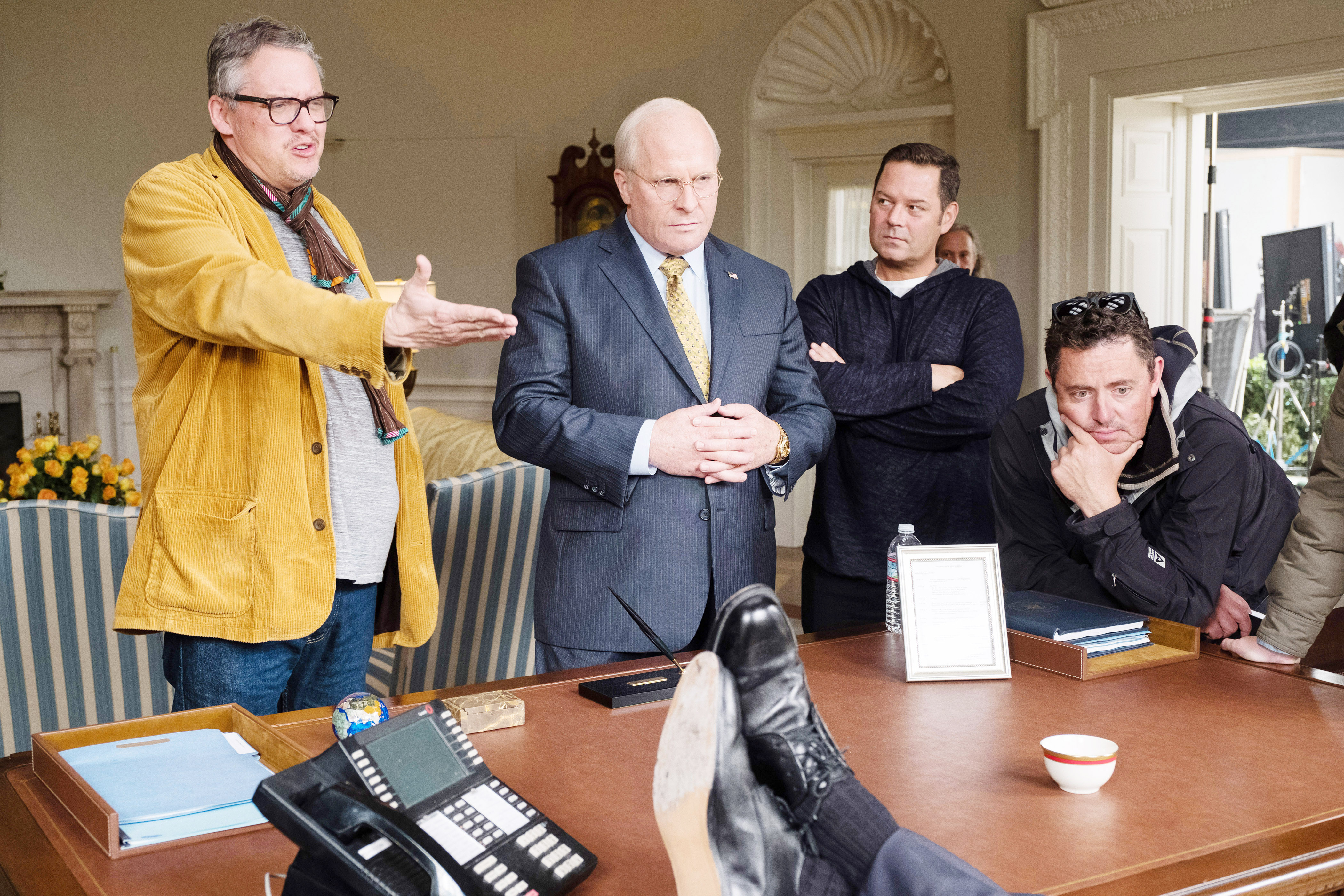 VICE, from left: director Adam McKay, Christian Bale as Dick Cheney, producer Kevin Messick, and cinematographer Greig Fraser on set, 2018. ph: Matt Kennedy / © Annapurna Pictures /Courtesy Everett Collection