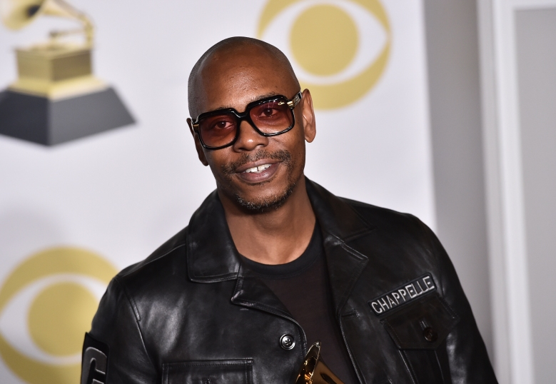 "FILE - In this Jan. 28, 2018 file photo, Dave Chappelle poses in the press room with the best comedy album award for ""The Age of Spin"" and ""Deep in the Heart of Texas"" at the 60th annual Grammy Awards in New York. Chappelle celebrated George Floyd's life and ripped the media for the way it handled his death in a surprise Netflix special. The special was released Thursday and is streaming free on Netflix's comedy YouTube channel.  (Photo by Charles Sykes/Invision/AP, File)"