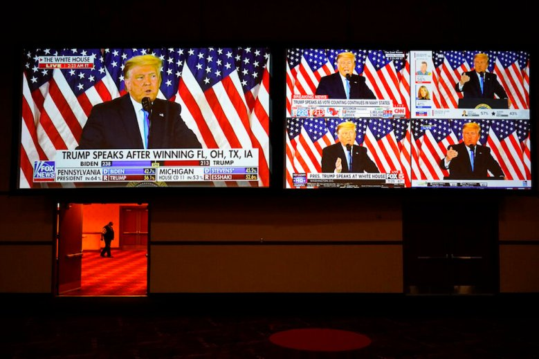 A live broadcast of President Donald Trump speaking from the White House is shown on screens at an election night party, Tuesday, Nov. 3, 2020, in Las Vegas. (AP Photo/John Locher)