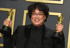 """FILE - Bong Joon Ho poses in the press room with the awards for best director for """"Parasite"""" and for best international feature film for """"Parasite"""" from South Korea at the Oscars in Los Angeles on Feb. 9, 2020. Bong Joon Ho won a total of four awards, including one for best original screenplay and best picture.  (Photo by Jordan Strauss/Invision/AP, File)"""