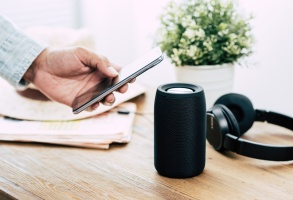 The man streams music from smartphone to bluetooth speaker.