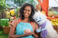 Michelle Obama, wearing a blue apron, stands in a rooftop garden posing for the camera and holding a pink, round mochi puppet. A bee puppet wearing a red tie hovers over her shoulder while a furry white and blue puppet with frozen waffle ears embraces her side.