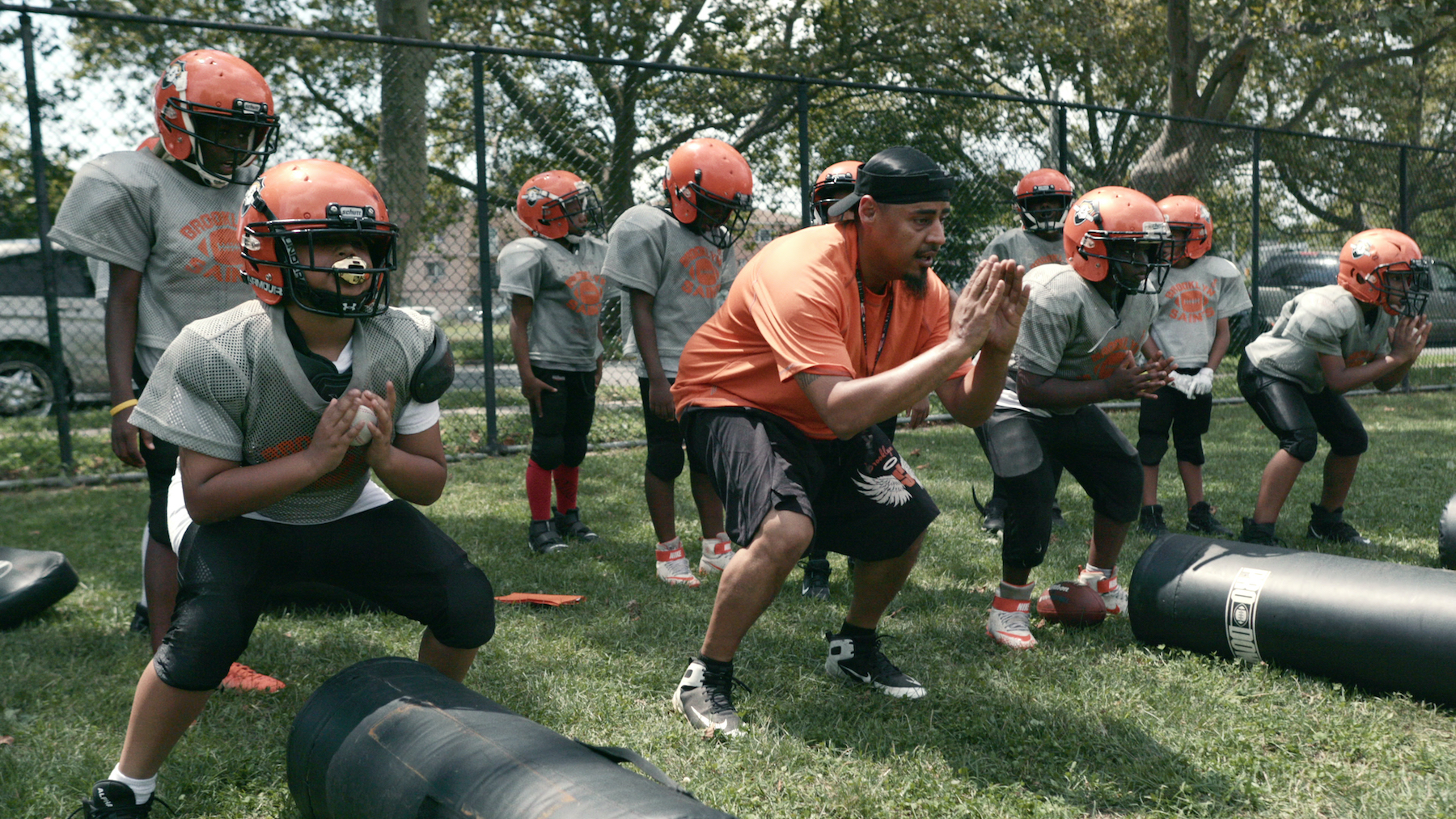 """Coach Gawuala (9U Coach) with the 9U team in episode 1 """"Welcome to the Saints Young Man"""" of We Are: The Brooklyn Saints S1. Cr. NETFLIX © 2021"""