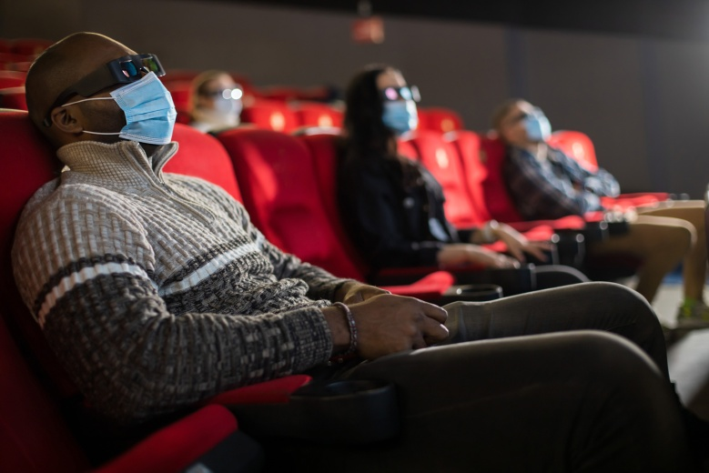 People sit in the cinema hall and watch a movie wearing medical masks and keep their distance. Covid-19 and the film industry.