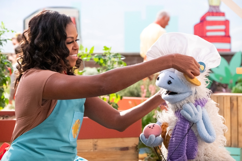 Michelle Obama, wearing a blue apron, sits in a rooftop garden and places a chef's hat on a furry white and blue puppet with frozen waffle ears, who is holding a pink, round mochi puppet.