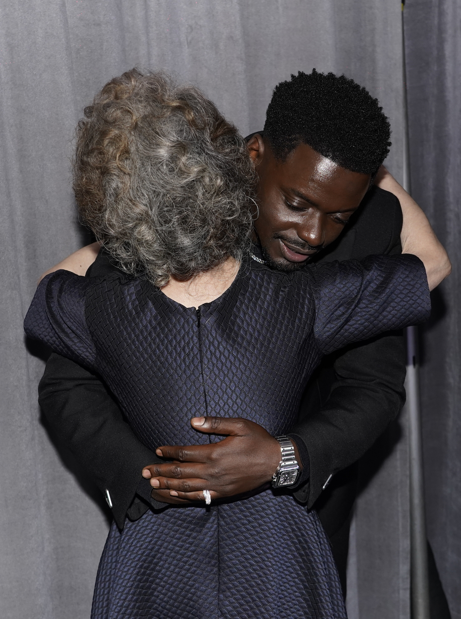 """Yuh-Jung Youn, left, winner of the award for best actress in a supporting role for """"Minari,"""" and Daniel Kaluuya, winner of the award for best actor in a supporting role for """"Judas and the Black Messiah,"""" hug outside the press room at the Oscars on Sunday, April 25, 2021, at Union Station in Los Angeles. (AP Photo/Chris Pizzello, Pool)"""