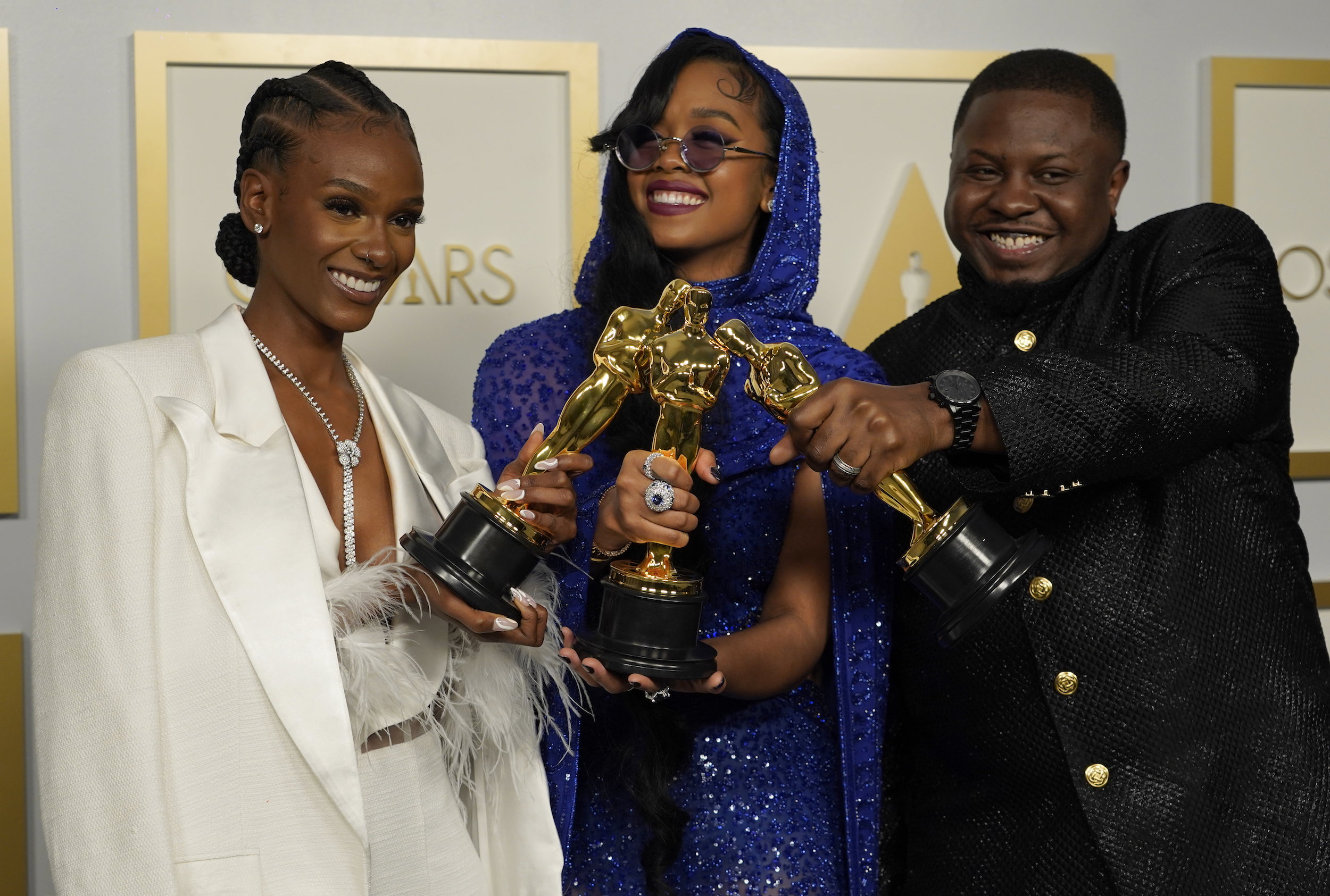 """Tiara Thomas, from left, H.E.R. and Dernst Emile II, winners of the award for best original song for """"Fight For You"""" from """"Judas and the Black Messiah,"""" pose in the press room at the Oscars on Sunday, April 25, 2021, at Union Station in Los Angeles. (AP Photo/Chris Pizzello, Pool)"""