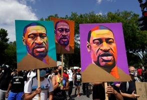 People carry posters with George Floyd on them as they march from the Lincoln Memorial to the Martin Luther King Jr. Memorial during the March on Washington, Friday Aug. 28, 2020, in Washington. (AP Photo/Carolyn Kaster)