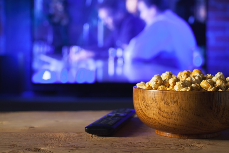 A wooden bowl of popcorn and the TV remote in the background the TV works. Evening cozy watching a movie or TV series at home.