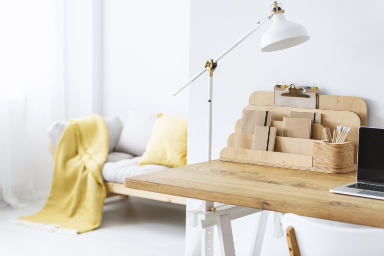 White lamp on wooden desk with laptop in freelance interior with organizer