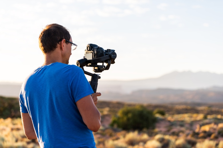 Man holding gimbal camera stabilizer filming valley view of sunrise with sunlight rays in Arches National Park, Utah, USA morning at Fiery Furnace Viewpoint