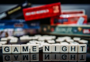 Game Night spelled out in letter tiles on black background with boardgames in the background