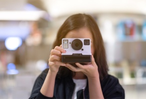 girl taking picture/using instant camera