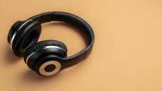 Stylish modern black chrome headphones over beige background