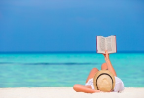 Young girl reading on tropical white beach