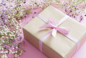 Pink background with lilac and white flowers and a present, mother's day concept
