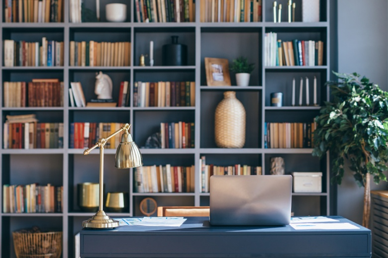 Table with laptop in home office book shelf