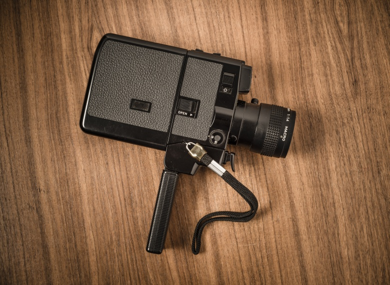Old retro 8 mm movie camera lying on wooden table. Film nostalgia containing old-fashioned home movie equipment. Can be used as a concepual image of classic old technology with a vintage look. There is only a close up of the object in the picture, no people are present.