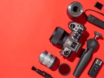Photographer workplace with dslr camera, lens, pen tablet and camera accessories on red background. Camera, photography, visual content