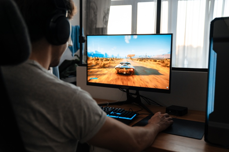 Caucasian brunette guy in headphones playing video game on his computer while sitting at home
