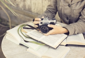 Girl with many open books and old style camera