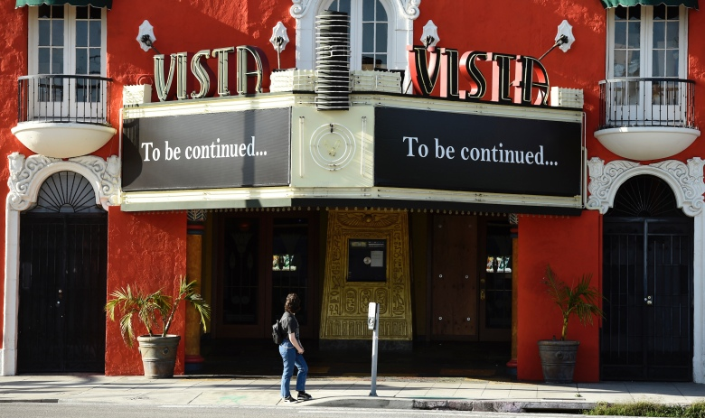 """CORRECTS DATE - A pedestrian looks up at a """"To be continued…"""" message on the marquee of the Vista movie theatre, Tuesday, April 21, 2020, in Los Angeles. Movie theaters remain closed as stay-at-home orders continue in California due to the coronavirus pandemic. (AP Photo/Chris Pizzello)"""