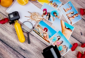 Beautiful photos of young girls in bathing suits and colorful bright hats on the sea and professional photographic equipment on a wooden table