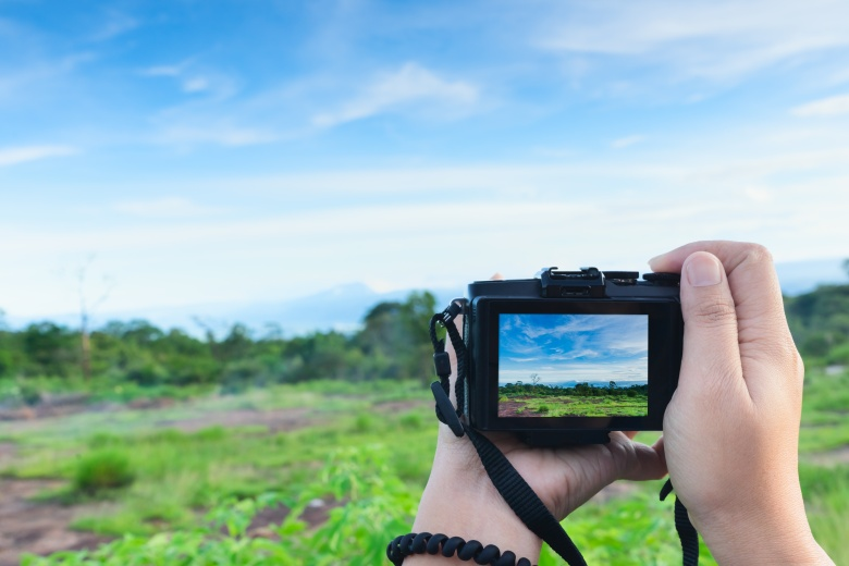 Traveller using mirrorless camera in hand, travel blogger, Close up of women's hands holding mirrorless camera taking picture at Phuhinrongkla to share on internet social media.