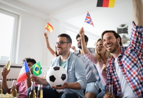 Cheerful and happy group of friends watching olympic games on tv at home