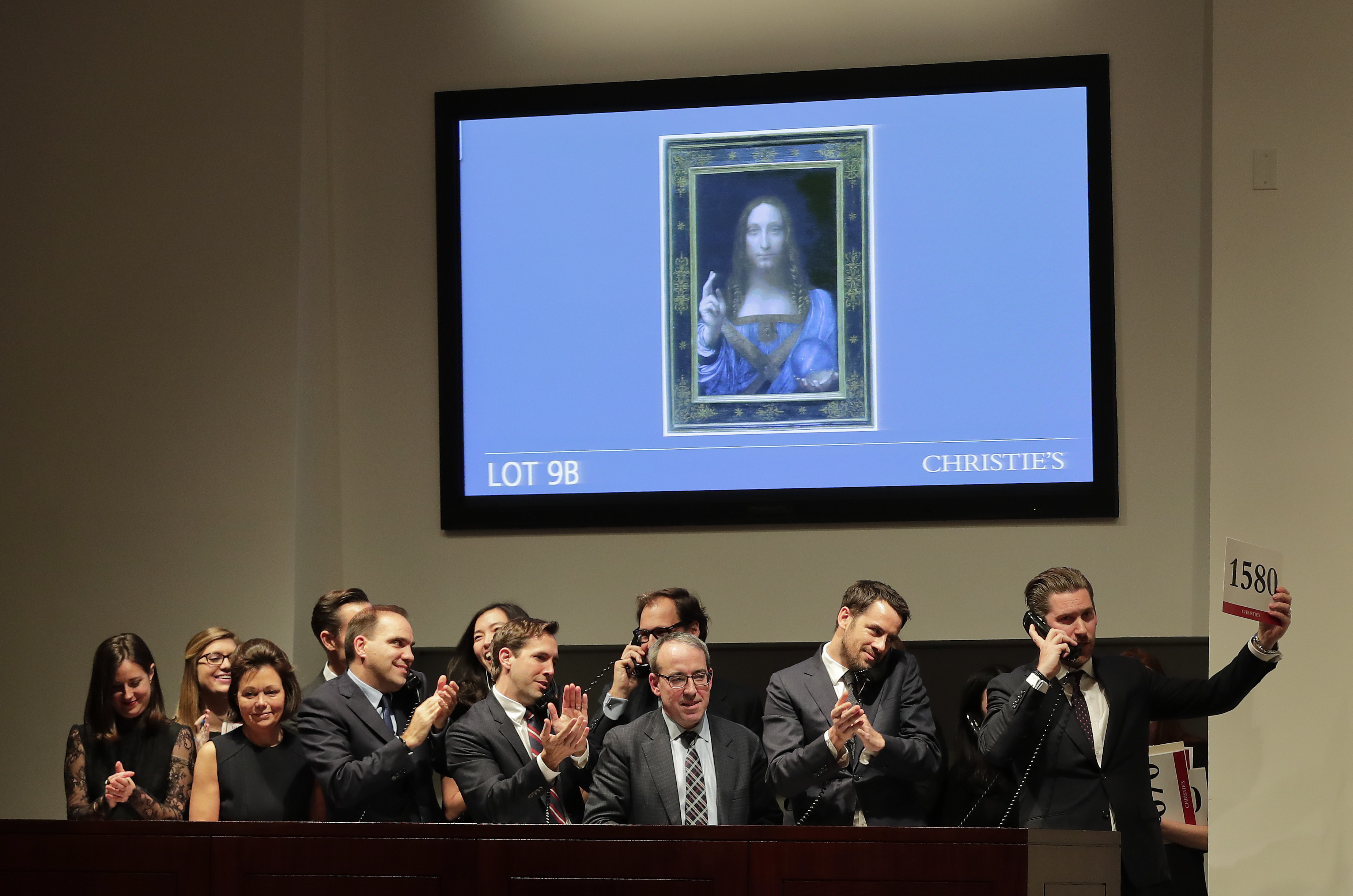 """FILE- In this Wednesday, Nov. 15, 2017 file photo, bidding representatives react after Leonardo da Vinci's """"Salvator Mundi"""" sold for dollars 450 million at Christie's, in New York. Abu Dhabi's Department of Culture and Tourism announced Wednesday June 27, 2018, that Leonardo da Vinci's Renaissance oil painting of Christ 'Salvator Mundi' will be put on display at The Louvre Abu Dhabi from Sept. 18. (AP Photo/Julie Jacobson, File)"""