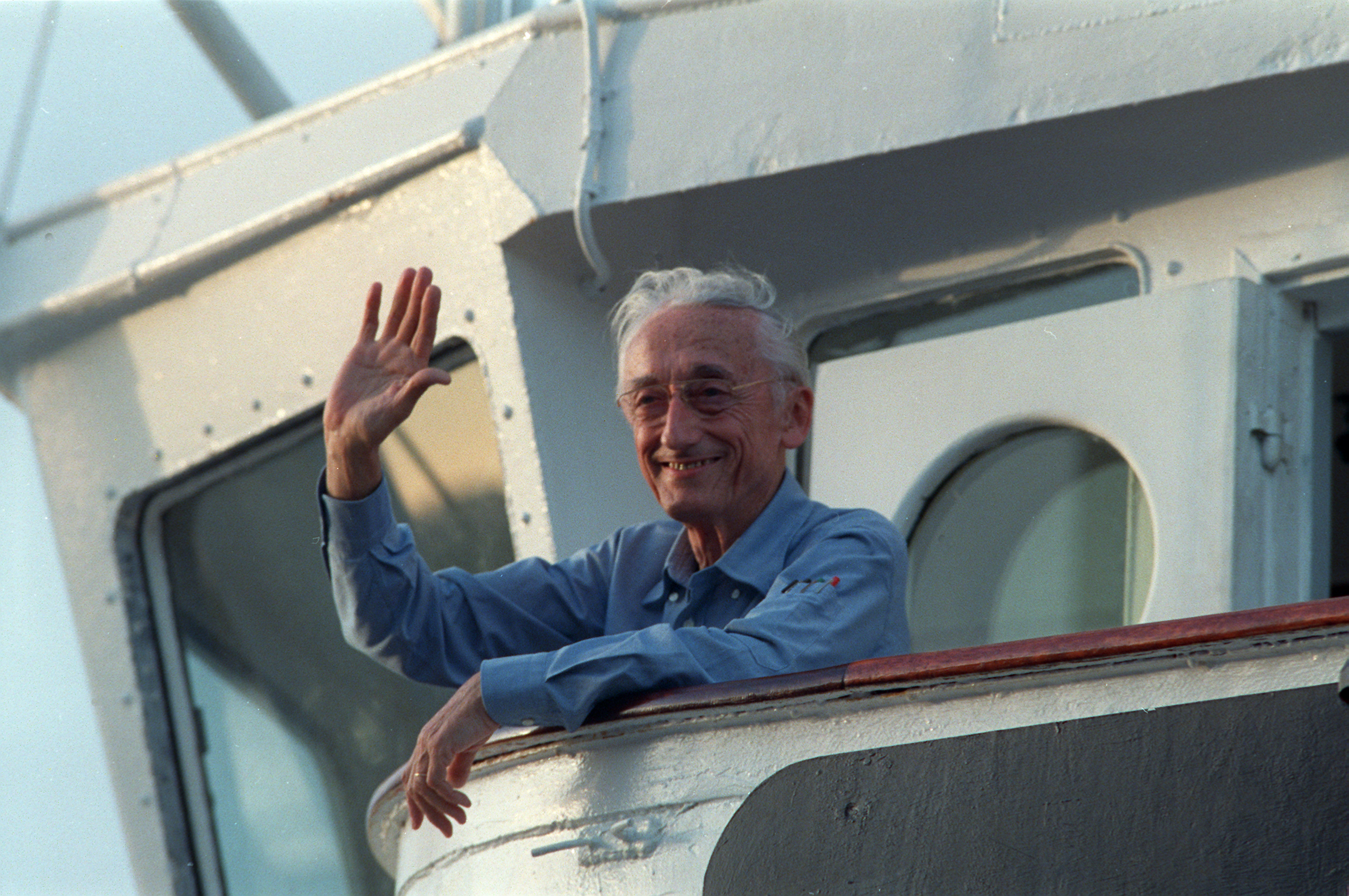 """Jacques-Yves Cousteau waves to onlookers aboard his ship Calypso as it pulls away from the dock to begin the second half of its """"Rediscover the World"""" trip in Miami, Fla., Wednesday, Aug. 27, 1986. Cousteau rode the ship just outside Government Cut in Miami before returning to shore. He plans to rejoin the vessel in 17 days in the South Pacific to study the damage done to the world's seas. (AP Photo/Doug Jennings)"""