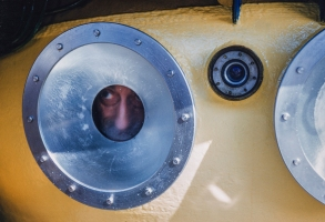 Jacques Cousteau peers out of the porthole of SP-350 Denise diving saucer, 1960. (Credit: National Geographic/Luis Marden)