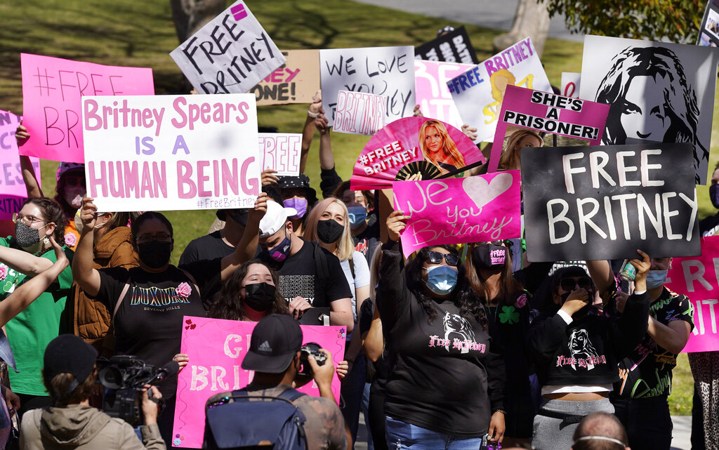 FILE - Britney Spears fans hold signs outside a court hearing concerning the pop singer's conservatorship at the Stanley Mosk Courthouse, March 17, 2021, in Los Angeles. Britney Spears' father agreed Thursday, Aug. 12, 2021, to step down from the conservatorship that has controlled her life and money for 13 years, according to reports. Several outlets including celebrity website TMZ and CNN reported that James Spears filed legal documents saying that while there are no grounds for his removal, he will step down. (AP Photo/Chris Pizzello, File)