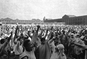 FILE - This Sept. 10, 1971 file photo shows inmates of Attica State Prison as they raise their hands in clenched fist salutes to voice their demands during a negotiating session with New York's prison Commissioner Russell Oswald. The whistleblower who spurred a major state investigation of alleged crimes and cover-ups at Attica prison is still on the case four decades later. Ex-prosecutor Malcolm Bell, now 82 and retired to the Green Mountains of Vermont, recently filed court papers in support of opening long-sealed investigation volumes. (AP Photo, File)