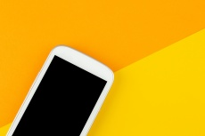 smart phone on yellow background with copy space