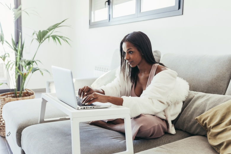 A young woman working from home with her laptop sitting on the sofa
