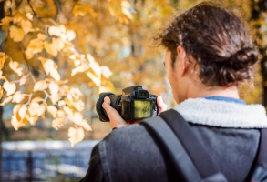 blogger/vlogger/student filmmaker video shooter filming colorful autumn park on his camera. Concept of autumn photo or video shootout