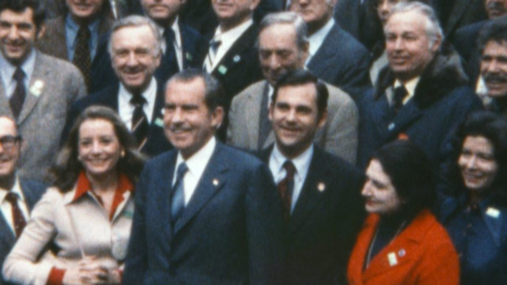 OUR NIXON, President Richard Nixon during his February 1972 trip to China, posing with reporters who accompanied him, including Dan Rather (bottom left), Barbara Walters (to Nixon's right), Walter Cronkite (directly behind Walters) and Helen Thomas (red suit), 2013. ©Cinedigm/courtesy Everett Collection