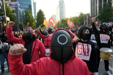 """Members of the South Korean Confederation of Trade Unions wearing masks and costumes inspired by the Netflix original Korean series """"Squid Game"""" shout slogans during a rally demanding job security in Seoul, South Korea, Wednesday, Oct. 20, 2021. Thousands of workers gathered ignoring the government's call to cancel the assembly feared to affect the fight against COVID-19. (AP Photo/Ahn Young-joon)"""