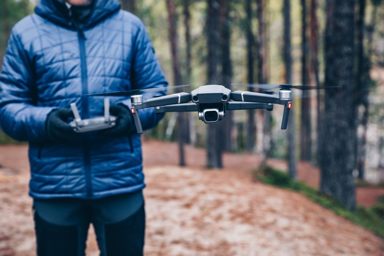 Man navigating a flying drone in fall forest.
